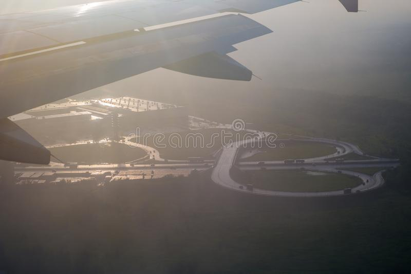 Vägföreningspunkt under vingen av flygplanet i de sista strålarna royaltyfri foto