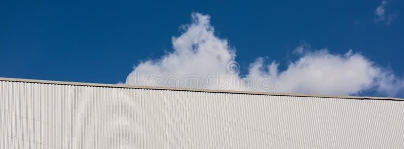 Vägg av en byggnad och blå himmel med ett vitt moln på en solig dag arkivfoto