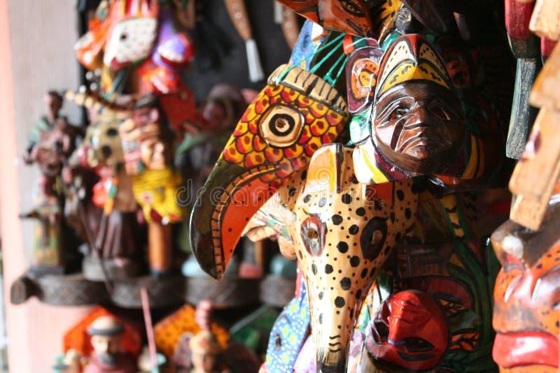 Vägg av maskeringar som är till salu i marknaden i Antigua Guatemala royaltyfri bild