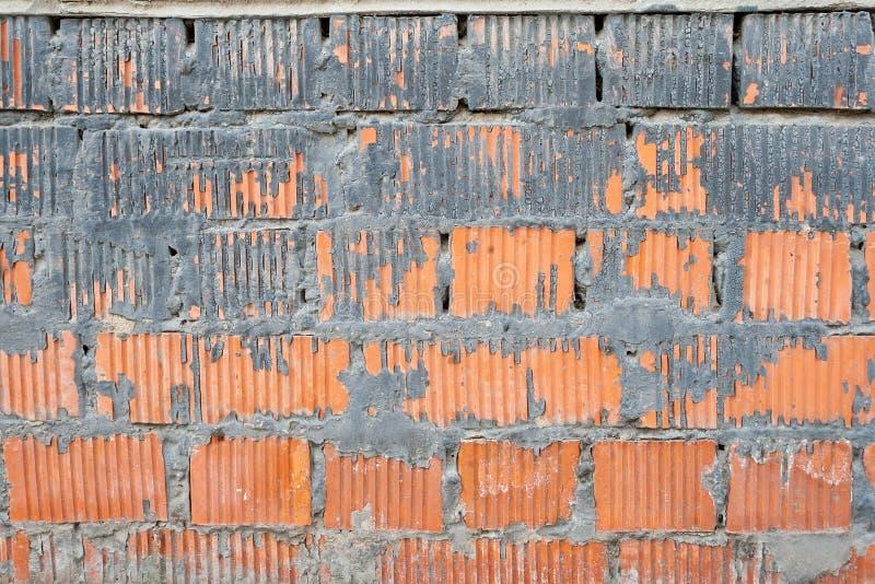 Vägg av orange randiga tegelstenar med ett tjockt lager av cement mellan och på dem arkivbild