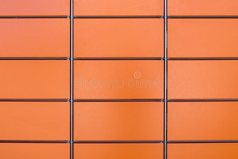 Vägg av rektangulära metalliska orange paneler arkivfoto
