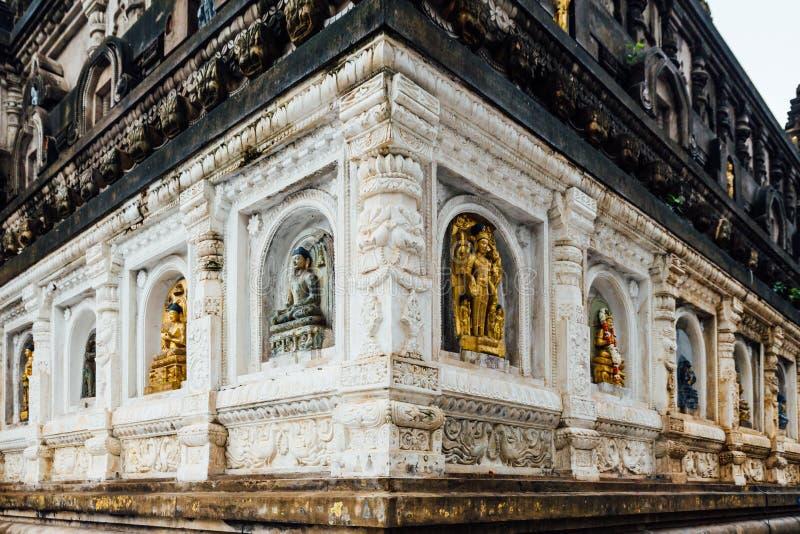 V?gg av templet som dekorerade med m?nga former och kulturer av antika Buddhastatyer p? den Mahabodhi templet p? Bodh Gaya royaltyfri bild