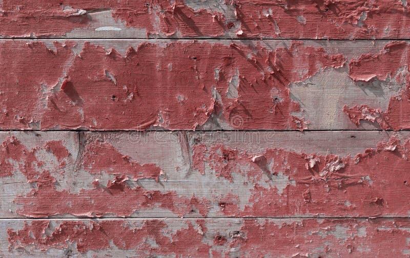 Vägg av träbräden med skalning av röd målarfärg royaltyfria bilder