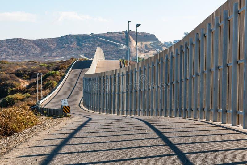 Vägg för internationell gräns mellan San Diego och Tijuana Extending in i avlägsna kullar royaltyfria foton