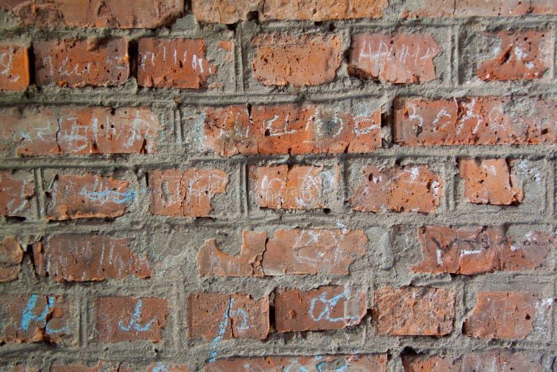 Vägg för röd tegelsten med inskrifter i krita arkivfoto