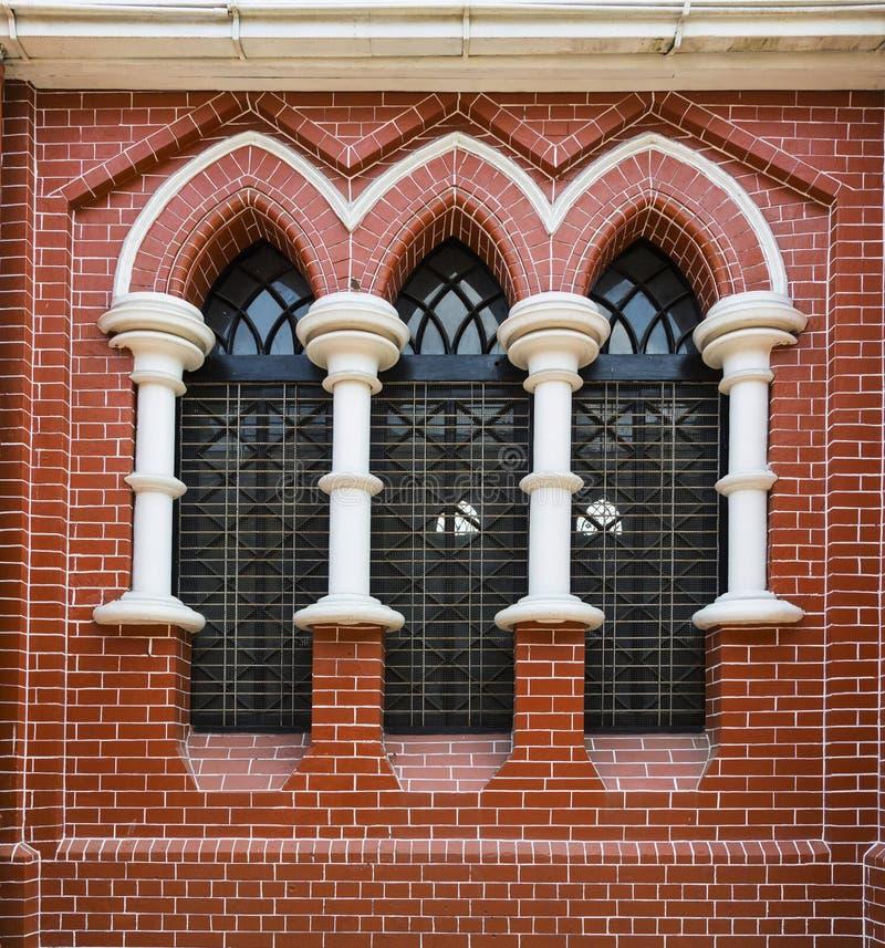 Vägg för röd tegelsten och målat glassfönster i domkyrka för helig trinity i Yangon, Myanmar, Burma arkivbild