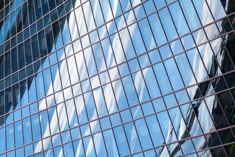 Vägg för skyskrapa för exponeringsglasspegel med blå himmel och det vita molnreflexionsslutet upp, modern sikt för affärsmitt royaltyfria foton