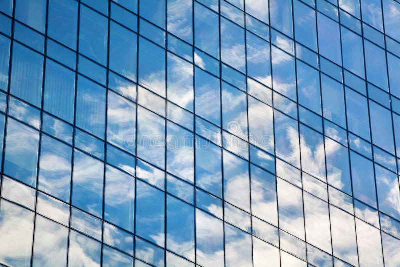 Vägg för skyskrapa för exponeringsglasspegel med blå himmel och det vita molnreflexionsslutet upp, modern sikt för affärsmitt arkivbild