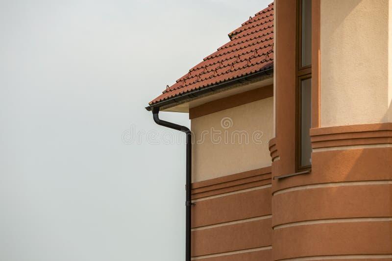 Vägg för stuckatur för närbilddetaljsida av den stora moderna dyra bostads- familjstugan med systemet för avloppsrännaregnrör på  royaltyfria bilder