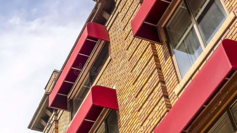 Vägg för tegelsten för sten för panoramarambyggnad yttre presentera och röda markiser på fönstren royaltyfria foton