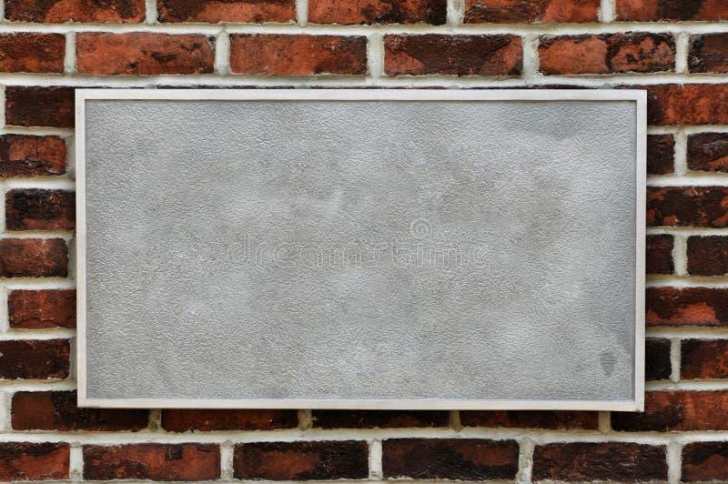 vägg för tegelstenmetalltecken arkivfoto