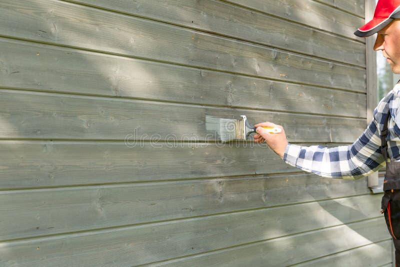 Vägg för trähus för manarbetarmålning yttre med skyddande färg för målarpensel och för trä arkivbilder