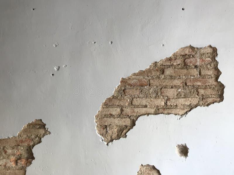 Vägg för vitt cement med sprucket utrymme som visar gamla bruna tegelstenar arkivfoton