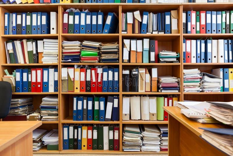 Vägg från hyllor med färgglade mapplimbindningar, ett kontorsrum med legitimationshandlingar och dokument royaltyfri bild