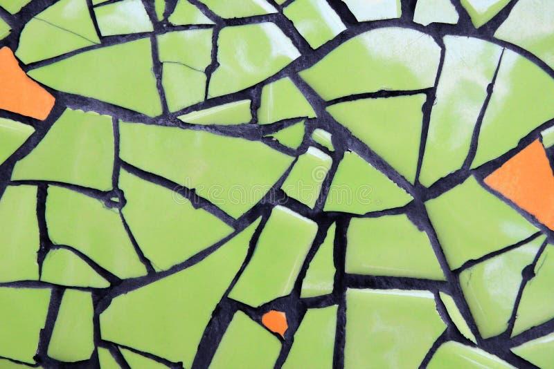 Vägg från keramiska stycken gräsplan och orange färg för bakgrund arkivfoto