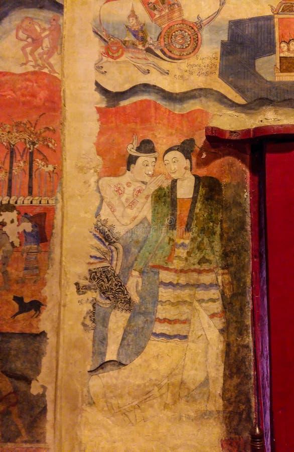 Vägg- målning av en man som viskar till örat av kvinnor i wat Phumin, nan, Thailand royaltyfria foton