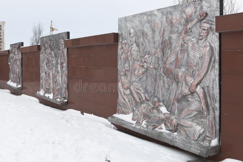 Vägg med bronsbasreliefer som visar de tragiska händelserna av krigstid på den minnes- komplexa `-Krasnaya Gorka `en i staden av  royaltyfria foton