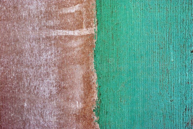Vägg med brunt och ljust - sjaskig målarfärg för grön turkos på vit bakgrund, bandskiljelinje på två halvor, grungetextur arkivbilder
