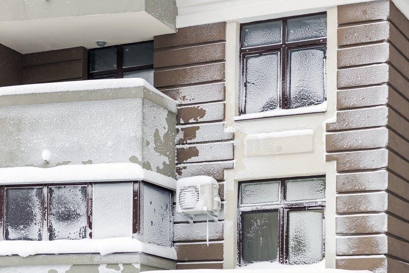 Vägg med fönster av modern höghushyreshus som täckas med snö och frost efter tungt blåsigt snöstormsnöfall och arkivbild