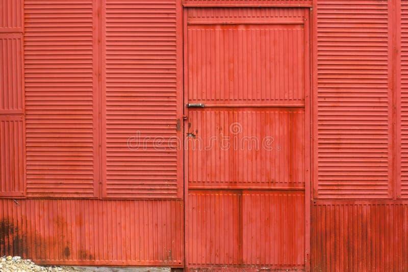 Vägg och dörr för rostig korrugerad metall röd royaltyfri foto