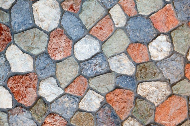 Vägg som göras av den naturliga mång--färgade stenen av ojämn form förbindelse av cement royaltyfri fotografi