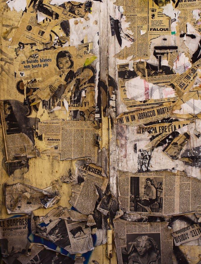 Vägg som skylas över brister med sönderrivna och gamla tidningar fotografering för bildbyråer