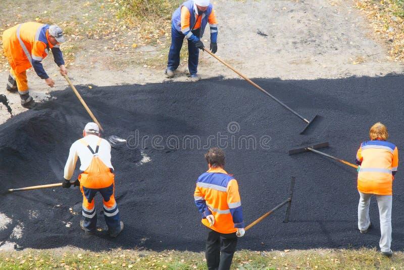 Väggata som reparerar arbeten Byggnadsarbetare under att asfaltera vägen royaltyfri foto
