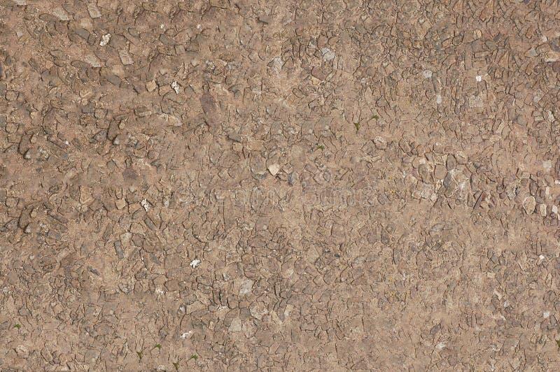 Väggen av brun färg göras av den lilla stenen Texturera eller bakgrund royaltyfria foton