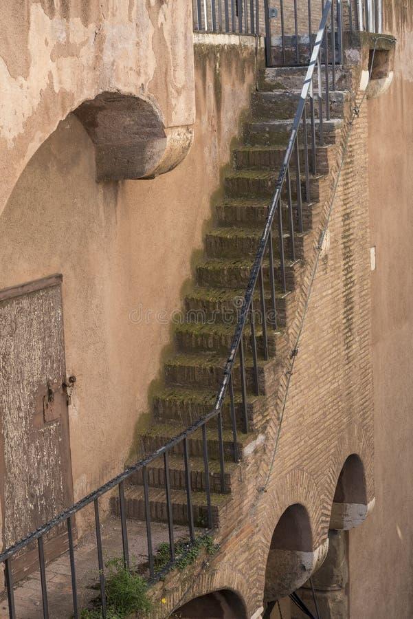 Väggen av byggnaden med en tegelstenvägg och en trappuppgång med metallräcke går ner arkivbild