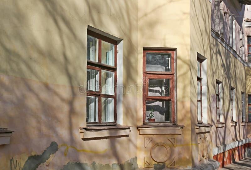 Väggen av det gamla två-våning huset med fjärden Windows royaltyfri bild