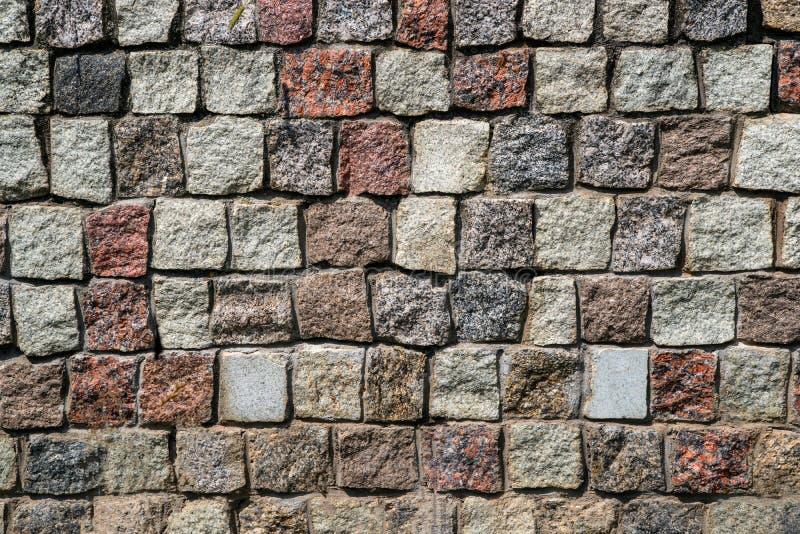 Väggen av fyrkantig granit stenar bakgrund arkivfoto