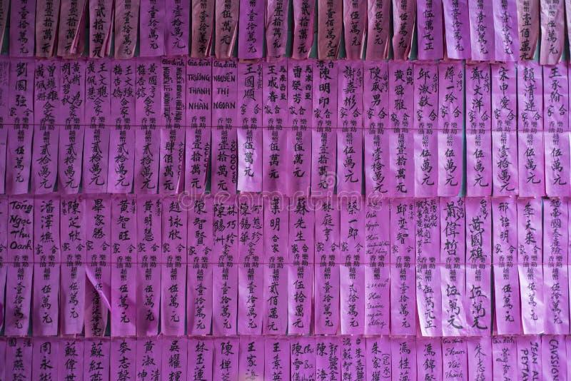 Väggen av purpurfärgad legitimationshandlingar visar namn av donatorer till templet i Ho CHien Minh City, Vietnam royaltyfri fotografi