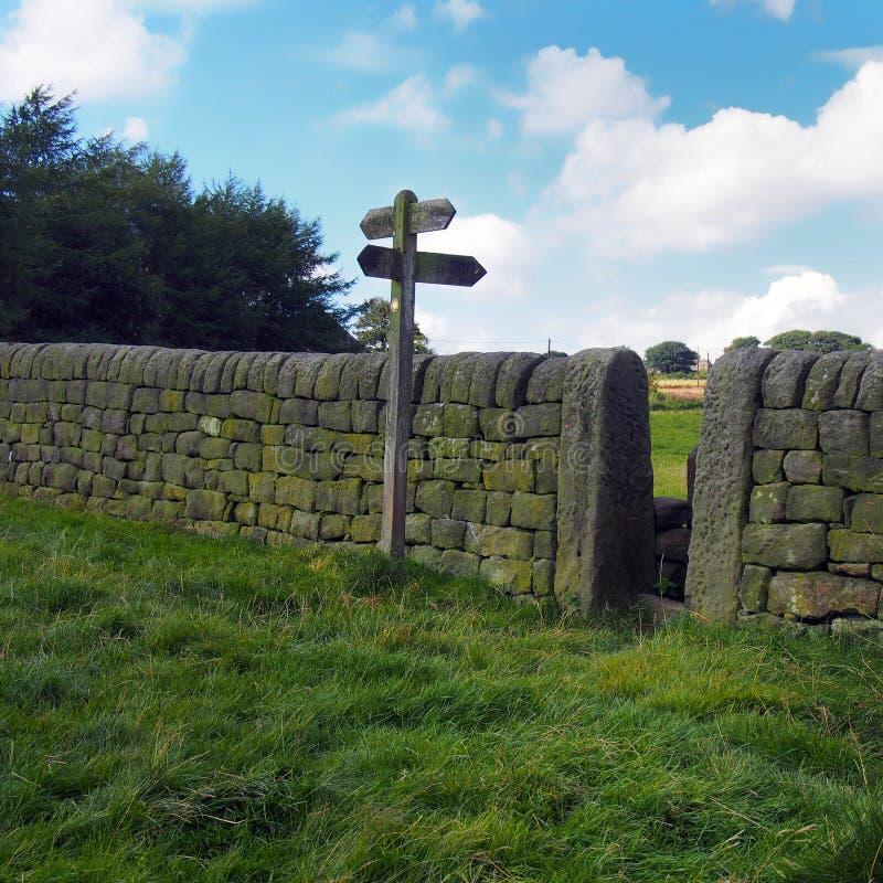 väggen för den torra stenen och att gå undertecknar in engelsk bygd royaltyfri bild