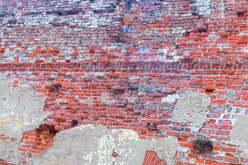 Väggen för tegelsten för väggtornet fördärvade den gamla den brutna stenen som täcktes mycket med den stads- murbrukbakgrundsdesi arkivfoton