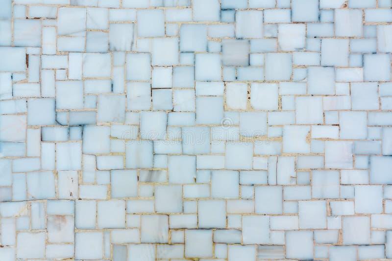 Väggen fodrade med litet ljust keramiskt eller marmorerar tegelplattor, textur royaltyfria bilder