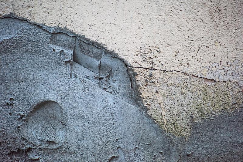 Väggen i sprickorna som rappas med cement arkivbild