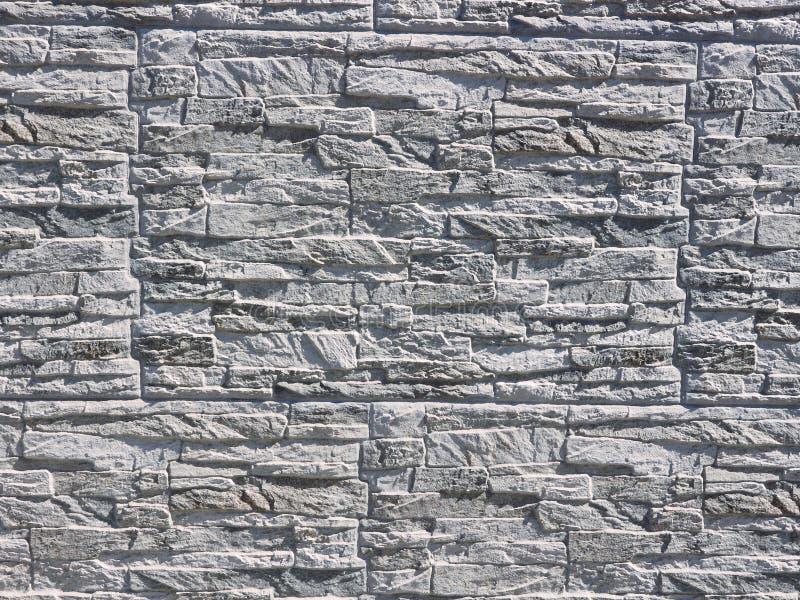 Väggen stenar cladding som göras av vitt, och grå färg vaggar, under solljuset royaltyfri foto