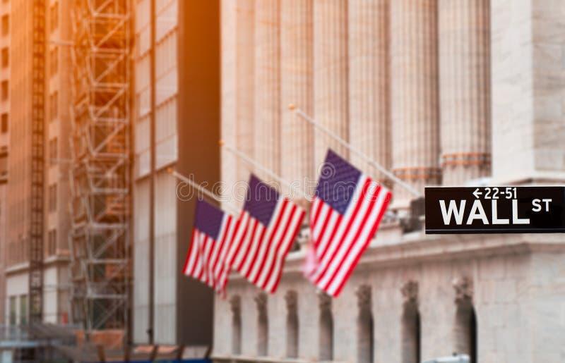 Vägggatan undertecknar in New York City med New York Stock Exchange bakgrund, USA royaltyfri foto