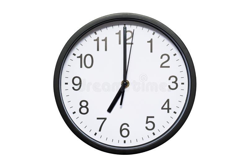 Väggklockan visar tid 7 klockan på vit isolerad bakgrund Rund väggklocka - främre sikt Nitton klockan arkivbild