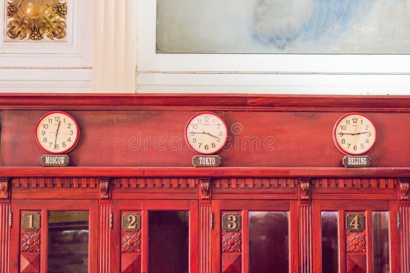 Väggklockor som visar tid i olika huvudstäder av världen royaltyfria bilder