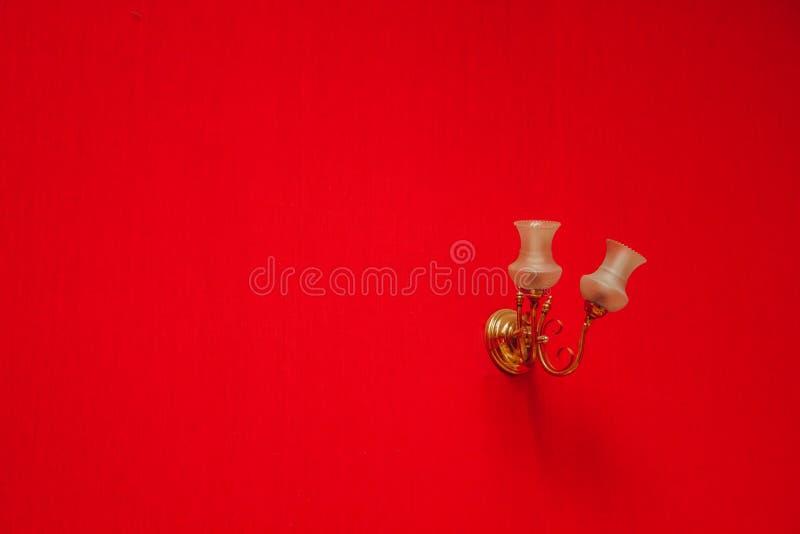 Vägglampa, lampett som hänger på väggen med den röda tapeten Textur f?r bakgrunden kopiera avst?nd fotografering för bildbyråer