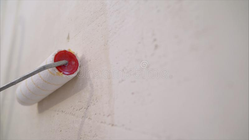 Väggmålarfärgrulle Rullborstemålning, arbetarmålning på rullborsten för skydd royaltyfri bild