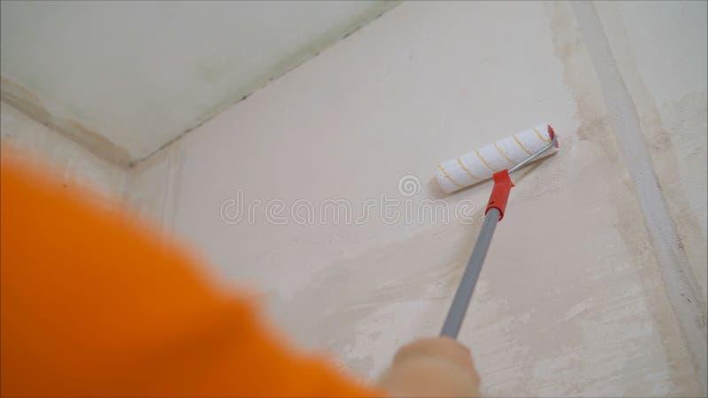 Väggmålarfärgrulle Rullborstemålning, arbetarmålning på rullborsten för skydd royaltyfri fotografi