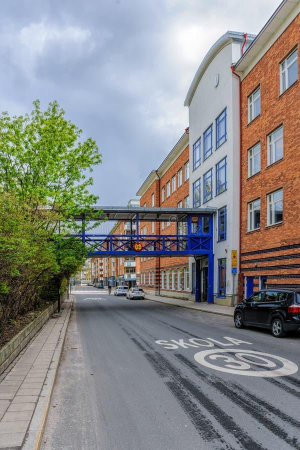 Vägmärke för hastighetsbegränsning 30 och skolaskolatecken på en väg i Stockholm med den fot- bron till skolabyggnaden över arkivbild