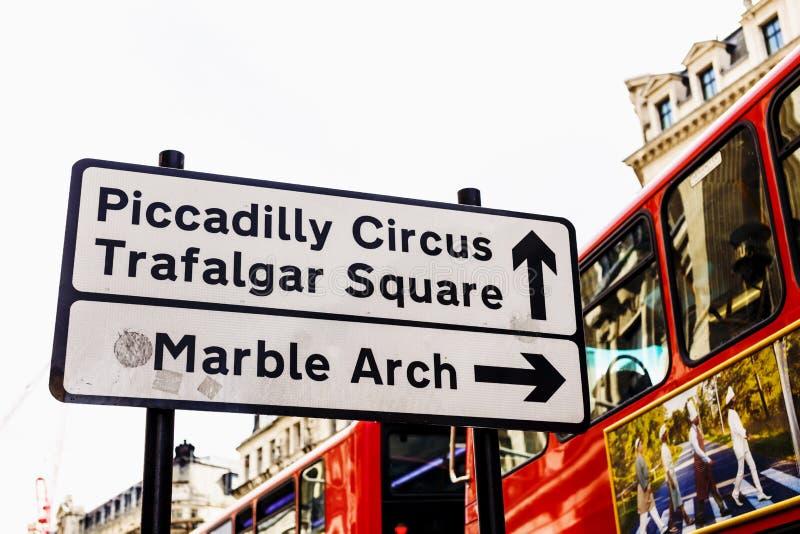 Vägmärke i London som listar berömda gränsmärken med den dubbla däckaren royaltyfria bilder