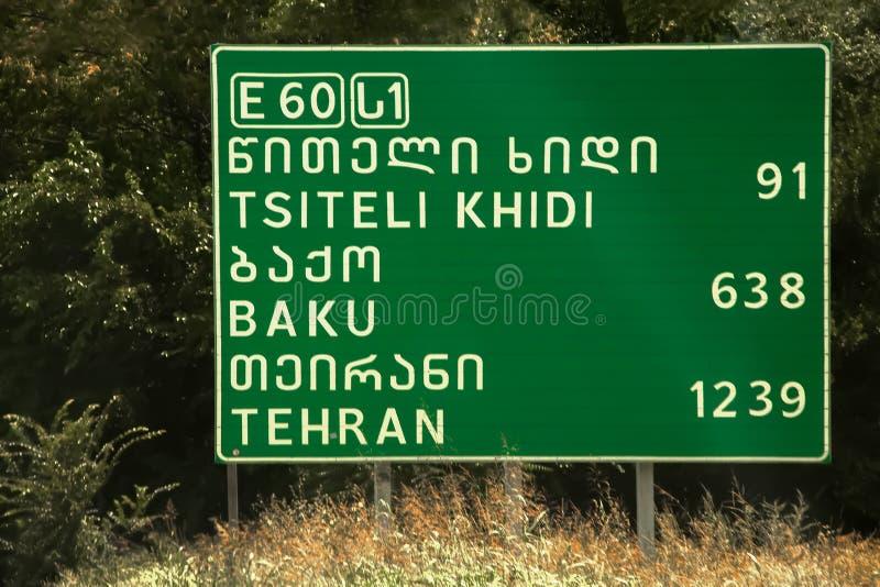 Vägmärke med avstånd till Baku och Teheran och Tsiteli Khidi i åtskilliga skrifter - nära Tbilisi Georgia royaltyfri foto