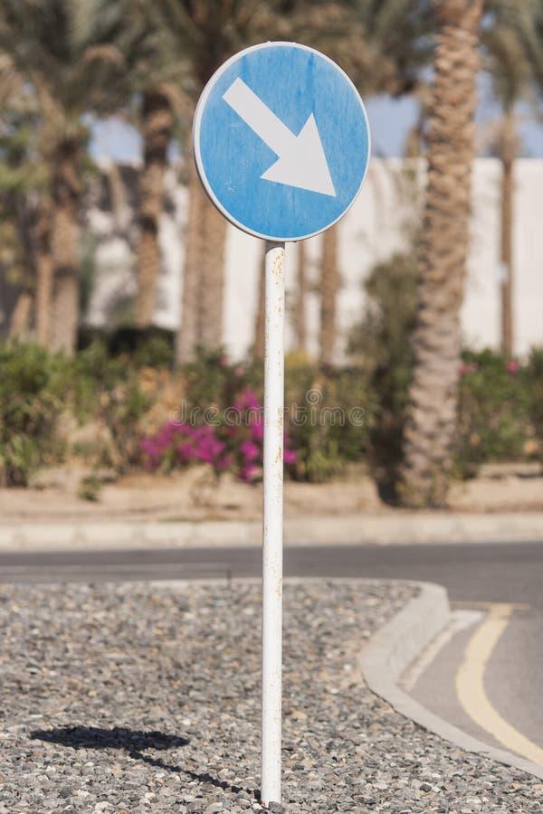 vägmärke`-omväg precis till den högra `en på vägen i semesterortområdet, på en dag med palmträd i bakgrunden arkivfoton