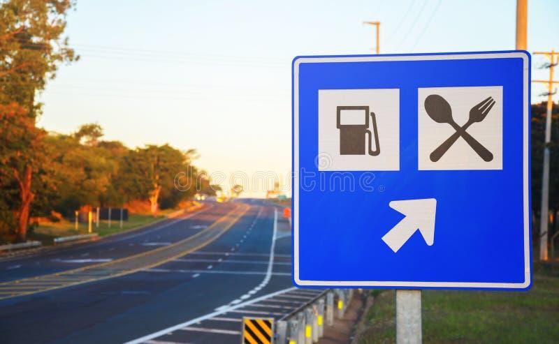 Vägmärke på vägrenen som signalerar en bensinstation- och matservi royaltyfri bild