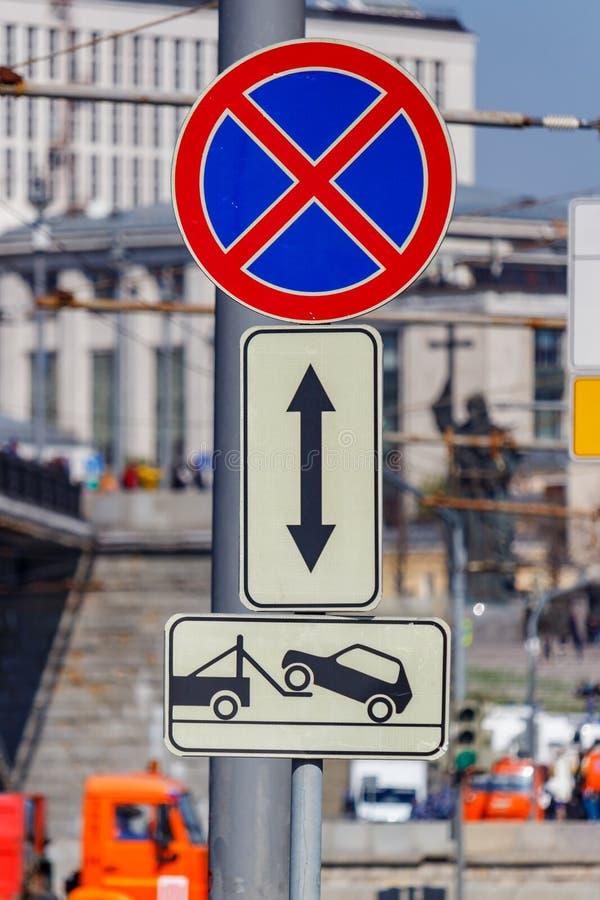 Vägmärke som förbjuder stoppa av bilen med en bärgningsbilskylt på stadsgatan i closeup för solig dag royaltyfria bilder