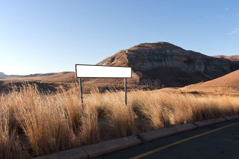Vägmärke under långt torrt gräs i torrt vinterlandskap arkivbilder